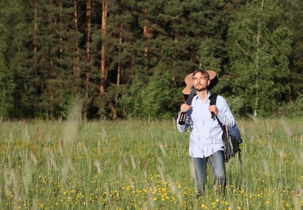 Uomo in piedi vicino a legno di pino con chitarra acustica e zaino. concetto di viaggio estivo