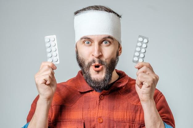 Uomo in pillole mediche che tengono le pillole in una mano