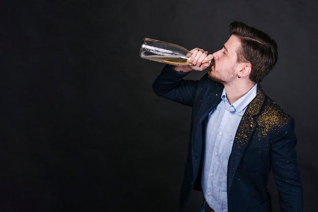 Uomo in polvere glitterata che beve champagne dalla bottiglia