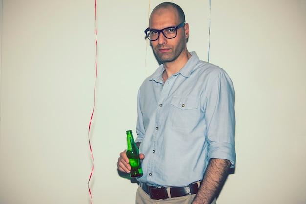 Uomo in posa con una birra alla festa