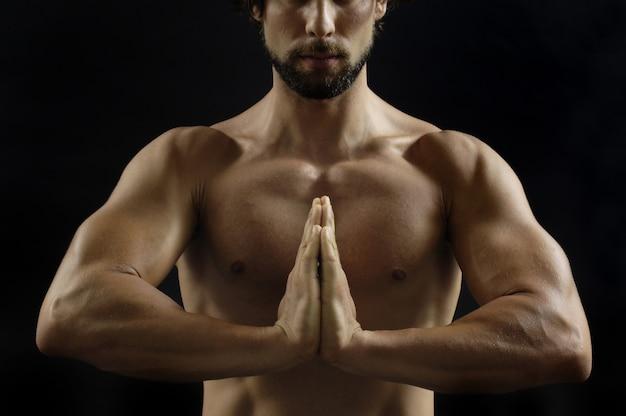 Uomo in posizione di meditazione su sfondo nero