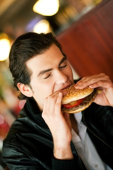 Uomo in ristorante che mangia hamburger