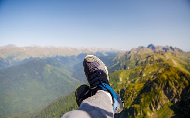 Uomo in scarpe da ginnastica e pittoresco paesaggio montuoso
