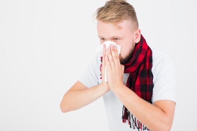 Uomo in sciarpa a scacchi che soffia il naso