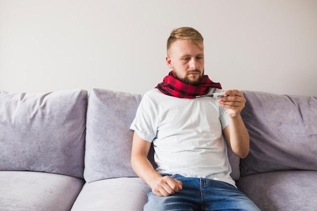 Uomo in sciarpa guardando il termometro