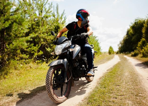 Uomo in sella a moto su strada sterrata con casco