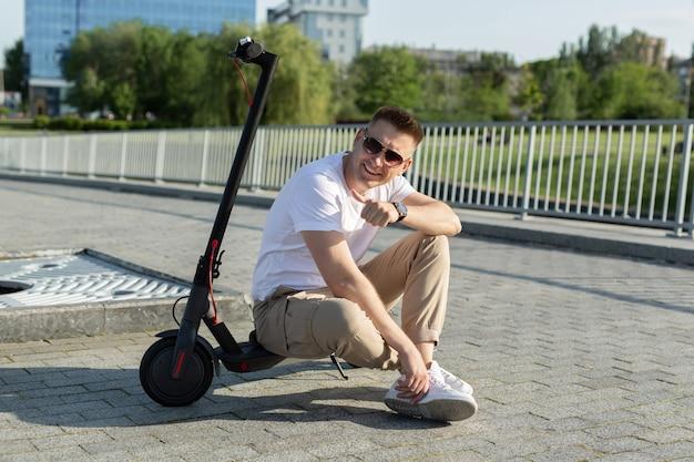 Uomo in sella a uno scooter elettrico per la città