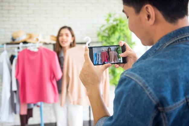 Uomo in streaming video in diretta da smartphone alla vendita di vestiti da fashion blogger