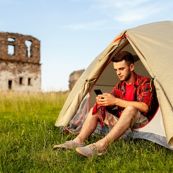 Uomo in tenda da campeggio che controlla cellulare