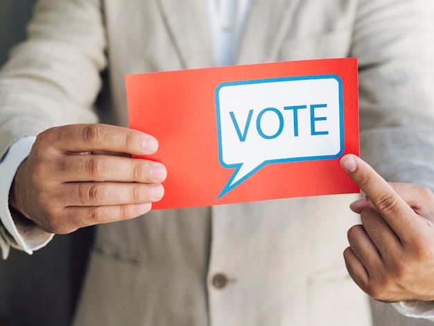 Uomo in tuta che punta a un messaggio di voto