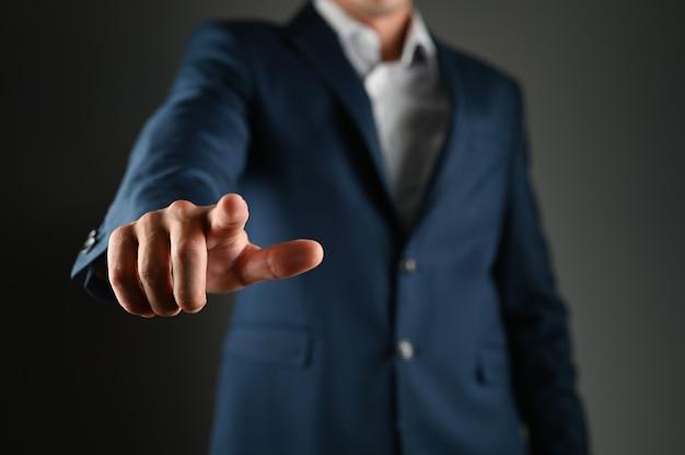 Uomo in tuta che punta il dito contro di te e la fotocamera, isolato su uno spazio buio. concetto di scelta. foto di alta qualità