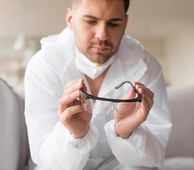 Uomo in tuta hazmat tenendo occhiali