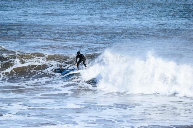 Uomo in tuta in neoprene che naviga su una grande onda