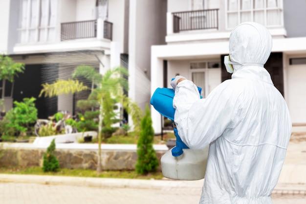 Uomo in tuta protettiva bianca che spruzza disinfettante sull'alloggiamento