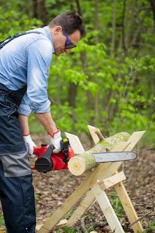 Uomo in tuta sega legno usando cavalletto con motosega nel bosco