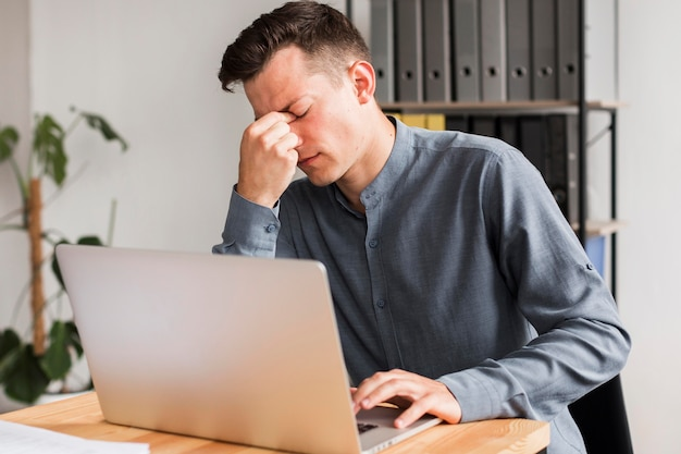 Uomo in ufficio durante la pandemia che sperimenta mal di testa