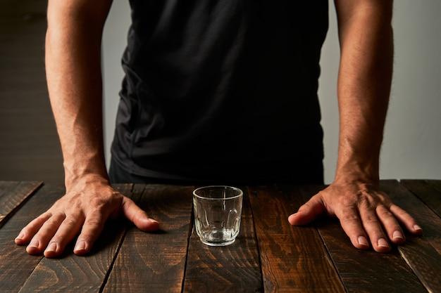 Uomo in un bar con un bicchierino. concetto di alcolismo e dipendenza.