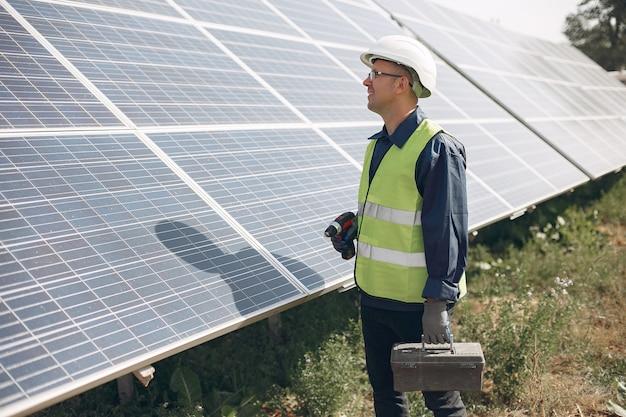 Uomo in un casco bianco vicino ad un pannello solare