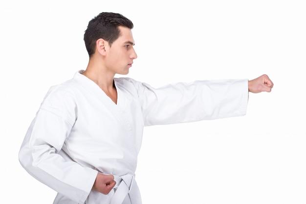 Uomo in un kimono che fa un pugno di karate