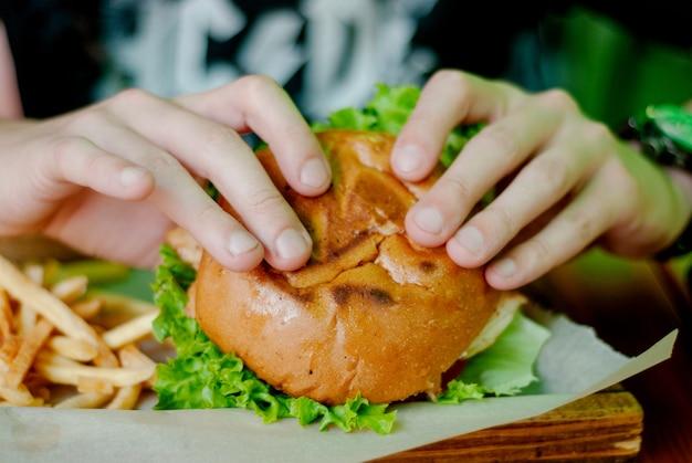 Uomo in un ristorante che mangia un hamburger