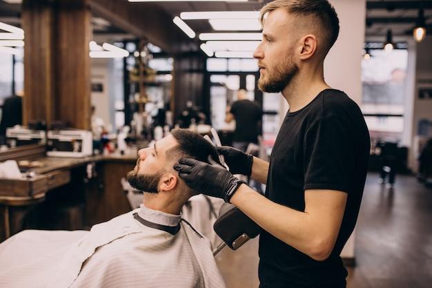 Uomo in un salone di barbiere facendo taglio di capelli e taglio della barba