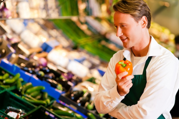 Uomo in un supermercato come commesso