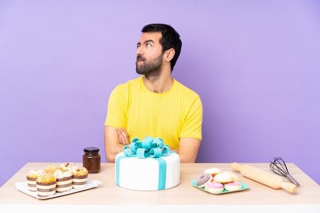 Uomo in un tavolo con una grande torta con espressione del viso confuso