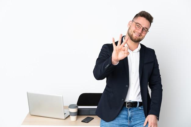Uomo in un ufficio isolato sulla parete bianca felice e contando tre con le dita