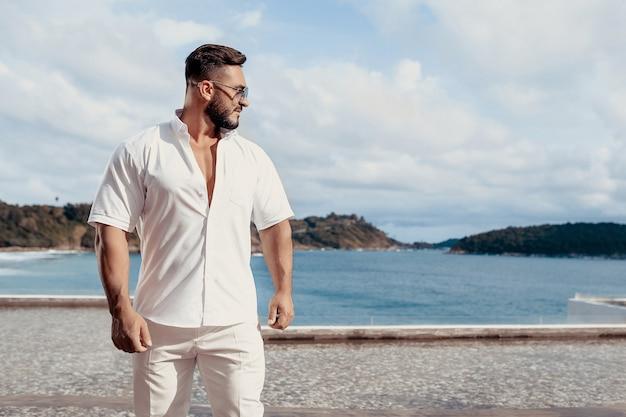 Uomo in una camicia bianca e pantaloni in piedi su una spiaggia