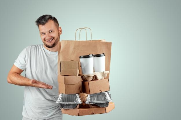 Uomo in una maglietta luminosa che dà un ordine degli alimenti a rapida preparazione isolato su una priorità bassa blu