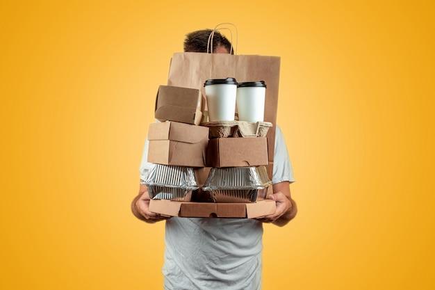 Uomo in una maglietta luminosa che dà un ordine degli alimenti a rapida preparazione isolato su una priorità bassa gialla