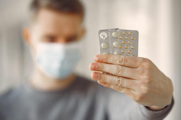 Uomo in una maschera che sta nella sala dell'ospedale