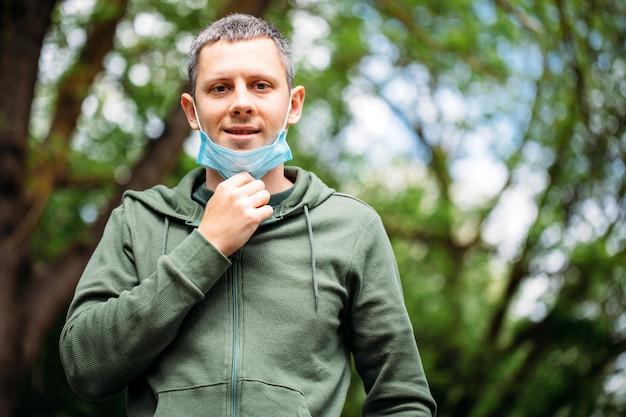 Uomo in una mascherina medica sulla natura. uomo che riposa nel parco dopo la quarantena covid-19