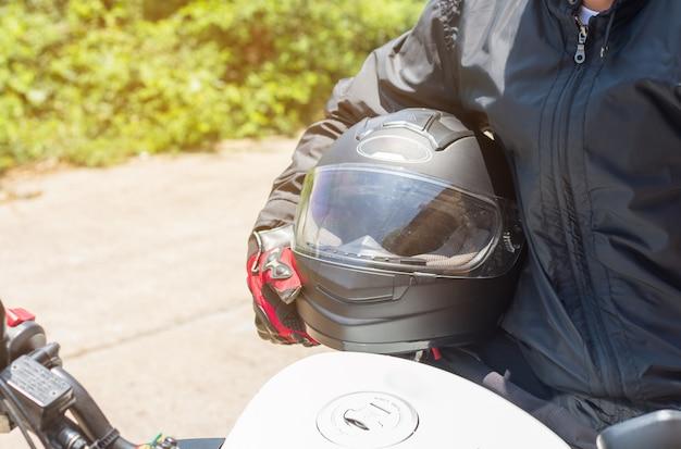 Uomo in una moto con casco e guanti indumenti protettivi per il motociclismo