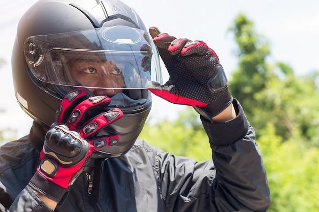 Uomo in una moto con casco e guanti indumenti protettivi per moto