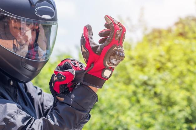 Uomo in una moto con indumenti protettivi casco e guanti
