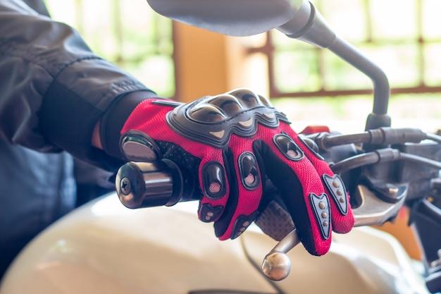 Uomo in una moto con indumenti protettivi per guanti per il controllo dell'acceleratore del motociclismo