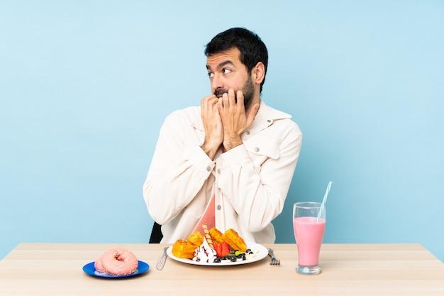 Uomo in una tabella con cibo guardando da un lato