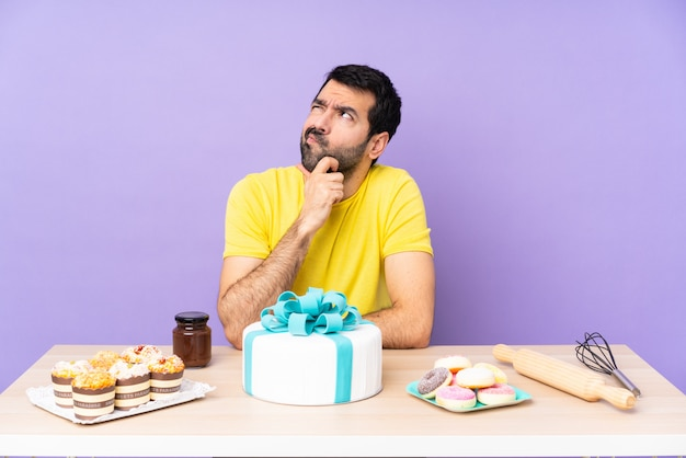 Uomo in una tabella con la grande torta sopra la parete viola isolata