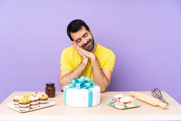 Uomo in una tabella con una grande torta che fa gesto di sonno nell'espressione dorable
