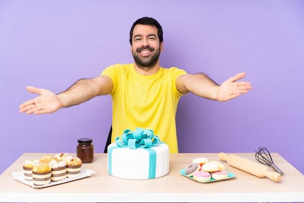 Uomo in una tabella con una grande torta che presenta e che invita a venire con la mano