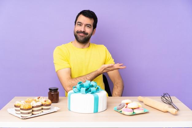Uomo in una tabella con una grande torta che presenta un'idea mentre sembra sorridere verso