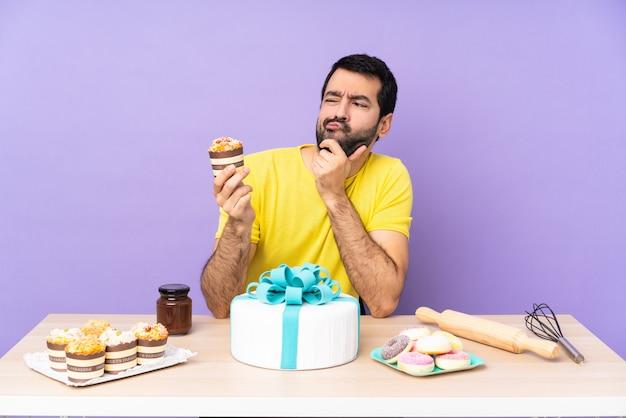Uomo in una tabella con una grande torta sopra la parete viola