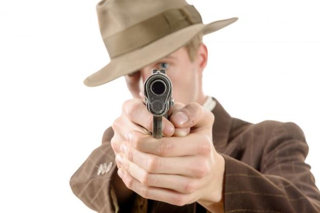 Uomo in una tuta vintage con una pistola