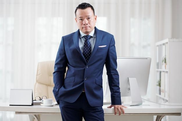 Uomo in vestito blu che si appoggia sulla sua tabella dell'ufficio per posare per un'immagine