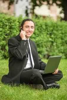 Uomo in vestito che si siede al prato inglese con il computer portatile.