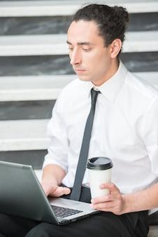 Uomo in vestito che si siede alle scale in ufficio e che per mezzo del computer portatile.