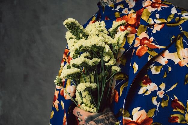 Uomo in vestito floreale che tiene il fiore giallo del limonium a disposizione