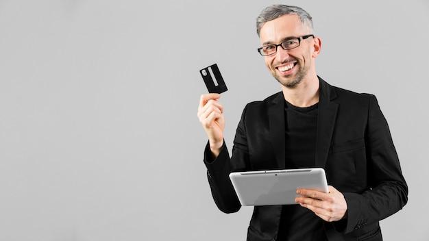 Uomo in vestito nero che mostra la carta di credito e la compressa