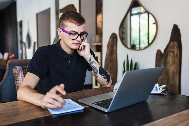 Uomo in vetri che lavora al computer portatile nel caffè